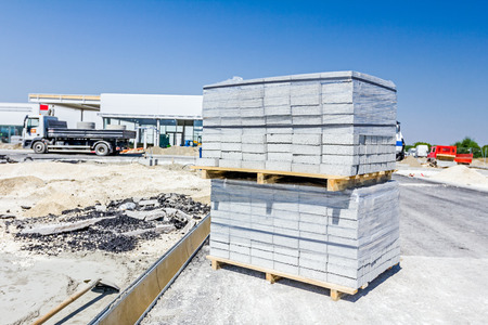 Wooden pallets with paving slabs are wrapped in plastic foil at building site.