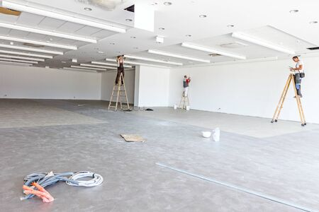 Communication or power cable is coming out from tiled floor. In background a team of workers electricians are using the wooden ladders to complete office ceiling with air duct and lamps.
