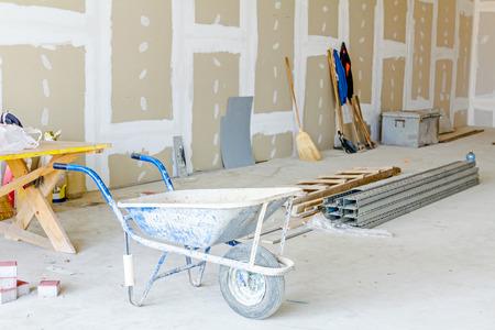 Schubkarre ist vor Werkzeuge für die Bodenarbeit. Dünne quadratische Metallprofile für trockene Wand auf dem Boden im Hintergrund gestapelt. Standard-Bild