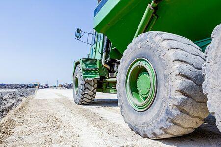 suelo arenoso: Gran camión volquete hidráulico se mueve sobre la tierra arenosa en obras de construcción. ángulo de visión baja