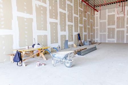 Kruiwagen staat voor gereedschappen voor grondwerk. De dunne vierkante metaalprofielen voor droge muur worden gestapeld op grond op achtergrond.