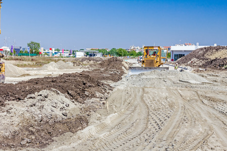 earthmover: Earthmover with caterpillars is moving earth at building site. Stock Photo