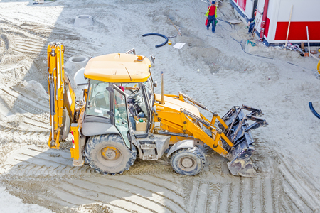compact track loader: Above view on excavator is moving ground at construction site. Stock Photo