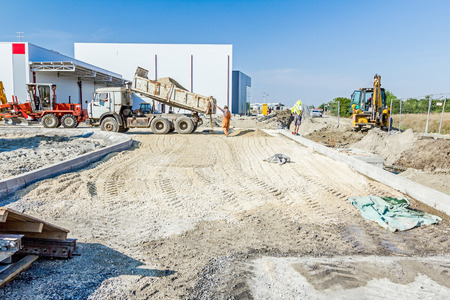 Dumper truck is unloading soil or sand at construction site. Landscape transform into urban area. Stock Photo - 66203707