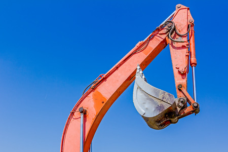Excavator has elevated high his bucket against blue sky.
