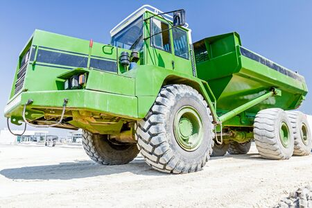 manage transportation: View on front end of big hydraulic dumper truck, going over sandy ground at building site.