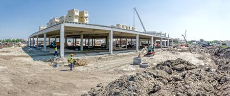Panorama está mostrando obra de construcción de maquinaria, la gente en el trabajo. Paisaje se transforma en área urbana grande, sala de hormigón.