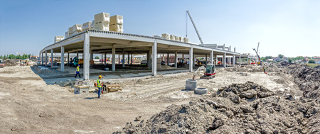 Panorama is showing construction site with machinery, people at work. Landscape transform into large urban area, concrete hall.