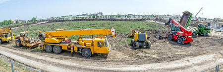 dumper: Panorama is showing the group of various machinery landscape transform. Yellow road roller with spikes, crane, cherry picker, telescopic forklift and dumper truck are parked in front of building site.