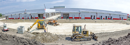 construction machinery: Zrenjanin, Vojvodina, Serbia - August 3, 2015: Panorama is taken at construction site, backhoe tractor is working on a construction site, digging a pit.