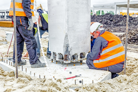 rigger: Zrenjanin, Vojvodina, Serbia - May 28, 2015: People are working to assembly concrete pillar on new edifice.