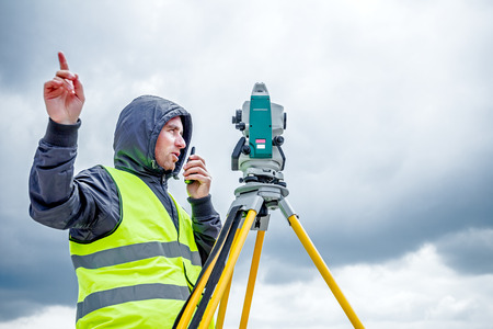 tachymeter: Zrenjanin, Vojvodina, Serbia - May 28, 2015: Surveyor engineer is measuring level on construction site. Surveyors ensure precise measurements before undertaking large construction projects.