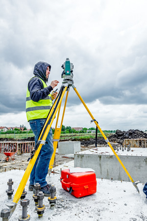 land surveying: Zrenjanin, Vojvodina, Serbia - May 28, 2015: Surveyor engineer is measuring level on construction site. Surveyors ensure precise measurements before undertaking large construction projects.
