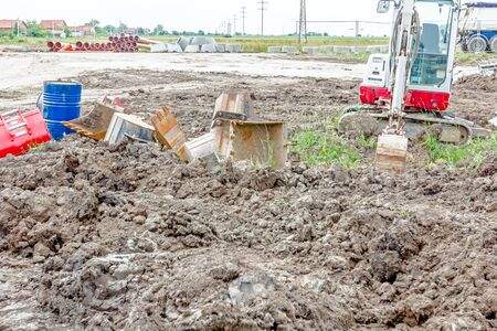 mini loader: Excavator buckets are lie scattered around on the ground, various types and many different sizes.