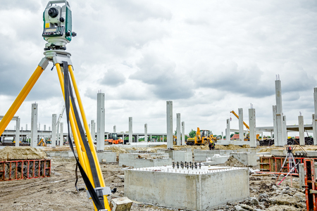 undertaking: Surveyor instrument is for measuring level on construction site. Surveyors ensure precise measurements before undertaking large construction projects. Stock Photo