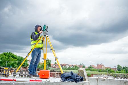 topografo: Zrenjanin, Vojvodina, Serbia - 28 may, 2015: ingeniero topógrafo está midiendo el nivel en el sitio de construcción. Los topógrafos que garantizan mediciones precisas antes de emprender grandes proyectos de construcción.