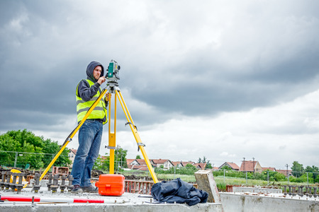tacheometer: Zrenjanin, Vojvodina, Serbia - May 28, 2015: Surveyor engineer is measuring level on construction site. Surveyors ensure precise measurements before undertaking large construction projects.