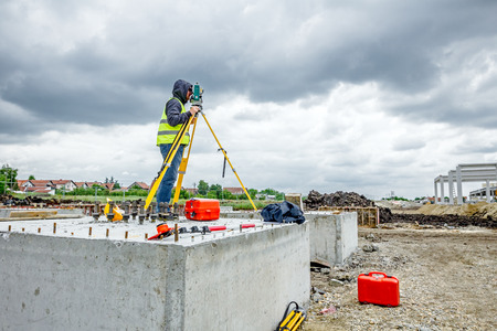 land surveying: Surveyor engineer is measuring level on construction site. Surveyors ensure precise measurements before undertaking large construction projects.