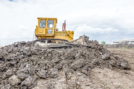 earthmover: View on heavy bulldozer while he moving, leveling ground at construction site.