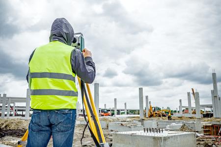 topografo: ingeniero topógrafo es la medición de nivel en el sitio de construcción. Los topógrafos que garantizan mediciones precisas antes de emprender grandes proyectos de construcción. Foto de archivo