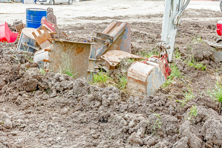 Excavator buckets are lie scattered around on the ground, various types and many different sizes.
