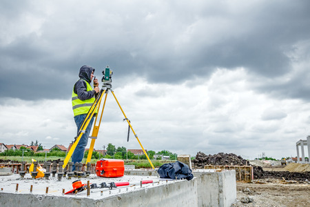 Zrenjanin, Vojvodina, Serbia - May 28, 2015: Surveyor engineer is measuring level on construction site. Surveyors ensure precise measurements before undertaking large construction projects.