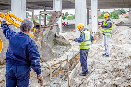 Zrenjanin, Vojvodina, Serbia - May 28, 2015: Workers are filling out with concrete armored shape, hole in ground using shovels. Editorial