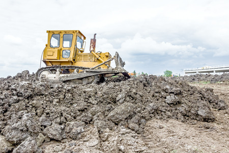 earthwork: View on heavy bulldozer while he moving, leveling ground at construction site.