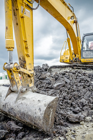 cargador frontal: Excavator is digging with his bucket against moody sky.