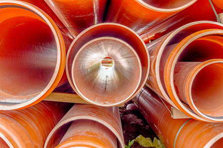 Arranged sewer pipes are waiting to be placed into the ditch at construction site. Stock Photo