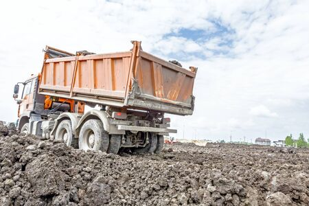 manage transportation: Big hydraulic dump truck is moving into reverse, prepare to unload cargo.