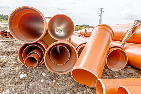Arranged sewer pipes are waiting to be placed into the ditch at construction site.  Standard-Bild