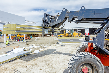 arms lifted up: Logistics concept, view on telescopic forklift that is carries composite panel walls at construction site.