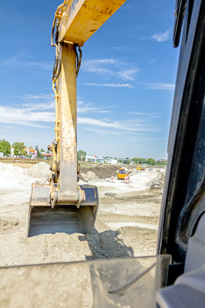 Excavator is digging with his bucket view from inside excavators cabin.
