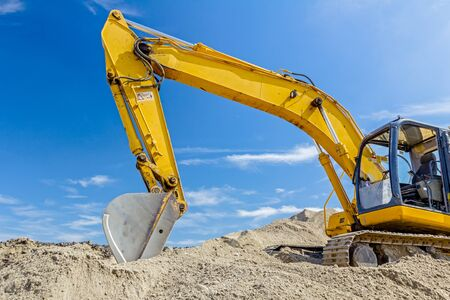 front end loader: Yellow excavator is making pile of soil by pulling ground up on heap at construction site, project in progress.