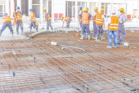 Bauarbeiter gießen Beton in Fundament bauen, Regie Pumpenrohr auf die richtige Richtung.
