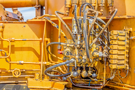 Hydraulic pressure pipes and connection fittings, levers, valves on control panel of industrial system on construction machinery. Archivio Fotografico