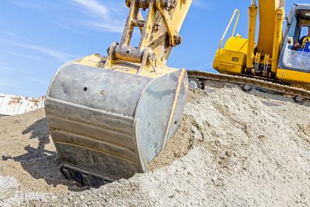 cargador frontal: Excavadora amarilla está haciendo pila de suelo tirando de abajo hacia arriba en el montón en el sitio de construcción, proyecto en curso.
