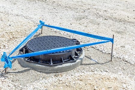 orifice: Three metal sticks with blue tape that is surrounding area around the fresh assembled new manhole with metal cover.