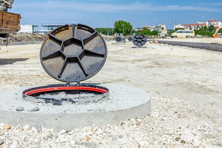 orifice: View on assembled new manhole with opened metal cover at construction site.
