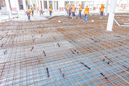 Construction workers are pouring concrete in building foundation, directing pump tube on the right direction. Editorial