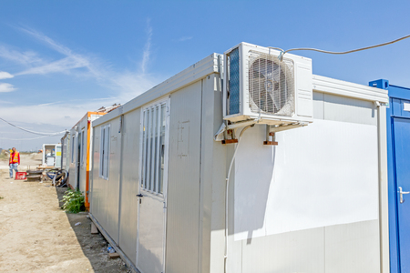backstop: Outdoor unit, compressor, of air conditioner is placed on container office.