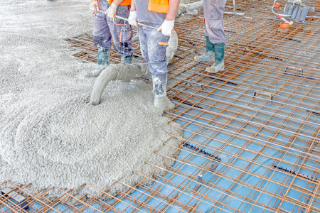 Construction workers are pouring concrete in building foundation, directing pump tube on the right direction. Stock fotó