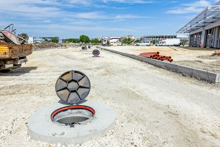 bunchy: View on assembled new manhole with opened metal cover at construction site.