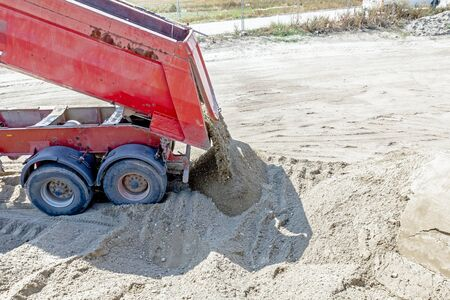 unloading: Red dumper truck is unloading sand at construction site.