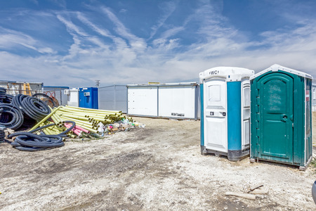 Two transportable public street toilets are placed at building site, outdoor privacy. Stock Photo