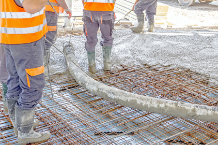 Construction workers are pouring concrete in building foundation, directing pump tube on the right direction. Stock Photo