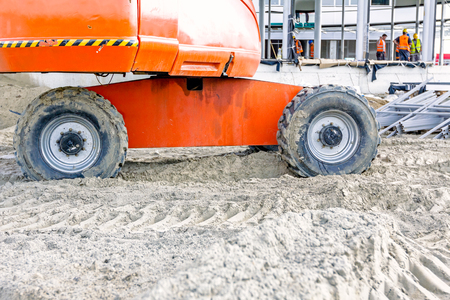 sandy soil: Low angle view on cherry pickers wheels at building site, undercarriage. Stock Photo