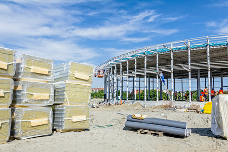 enveloped: Wall insulation, composite panels classified by the according to size and shape are wrapped in foil at construction site. Editorial