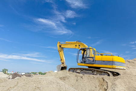 Yellow excavator is making pile of soil by pulling ground up on heap at construction site, project in progress.